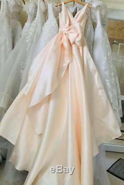Minimalistic satin wedding dress or ball gown in blush coral with big bow detail